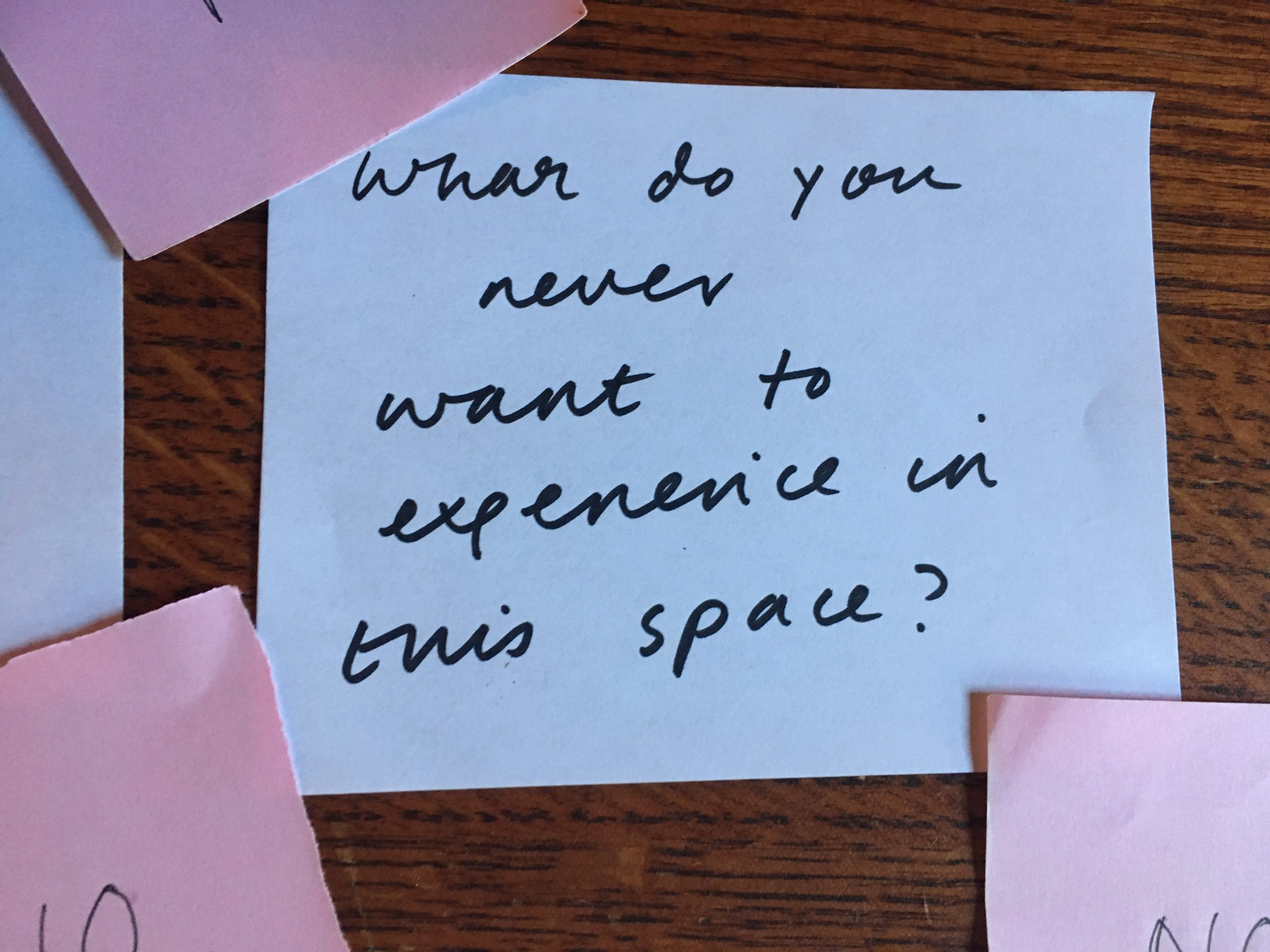 """A scrap of white paper surrounded by pink Post-It notes reads in handwriting, """"what do you never want to experience in this space?"""""""