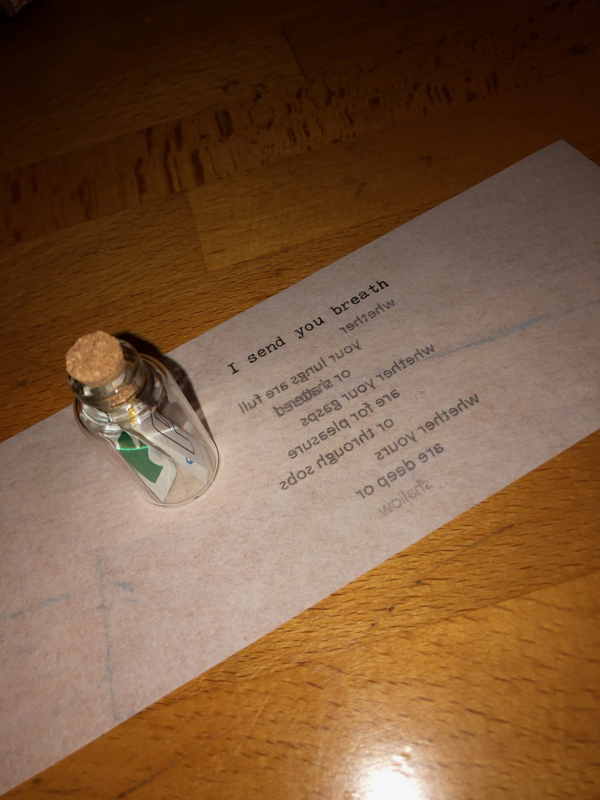 "Image of a miniature bottle with a note inside, and a strip of transparent paper on a wooden surface. The transparency is upside down, so the words read backwards: ""I send you breath/ whether/ your lungs are full/ or shattered/ whether your gasps/ are for pleasure/ or through sobs/ whether yours/ are deep or/ shallow""."